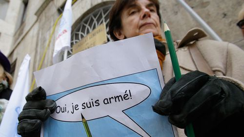 """A woman holds a pencil and a poster reading in French """"Yes, I am armed"""" during a rally in support of Charlie Hebdo, a French satirical weekly newspaper that fell victim to a terrorist attack, in front of the French Consulate in Milan, Italy. (AAP)"""