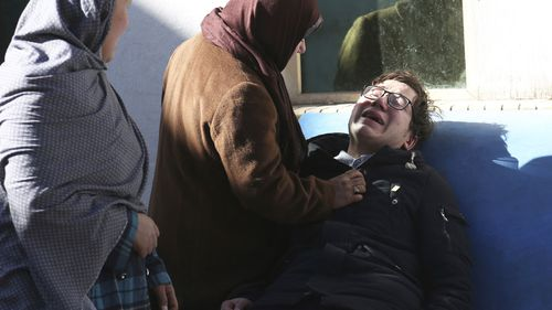 Two women console a man outside a hospital following a suicide attack in Kabul, Afghanistan. (AAP)