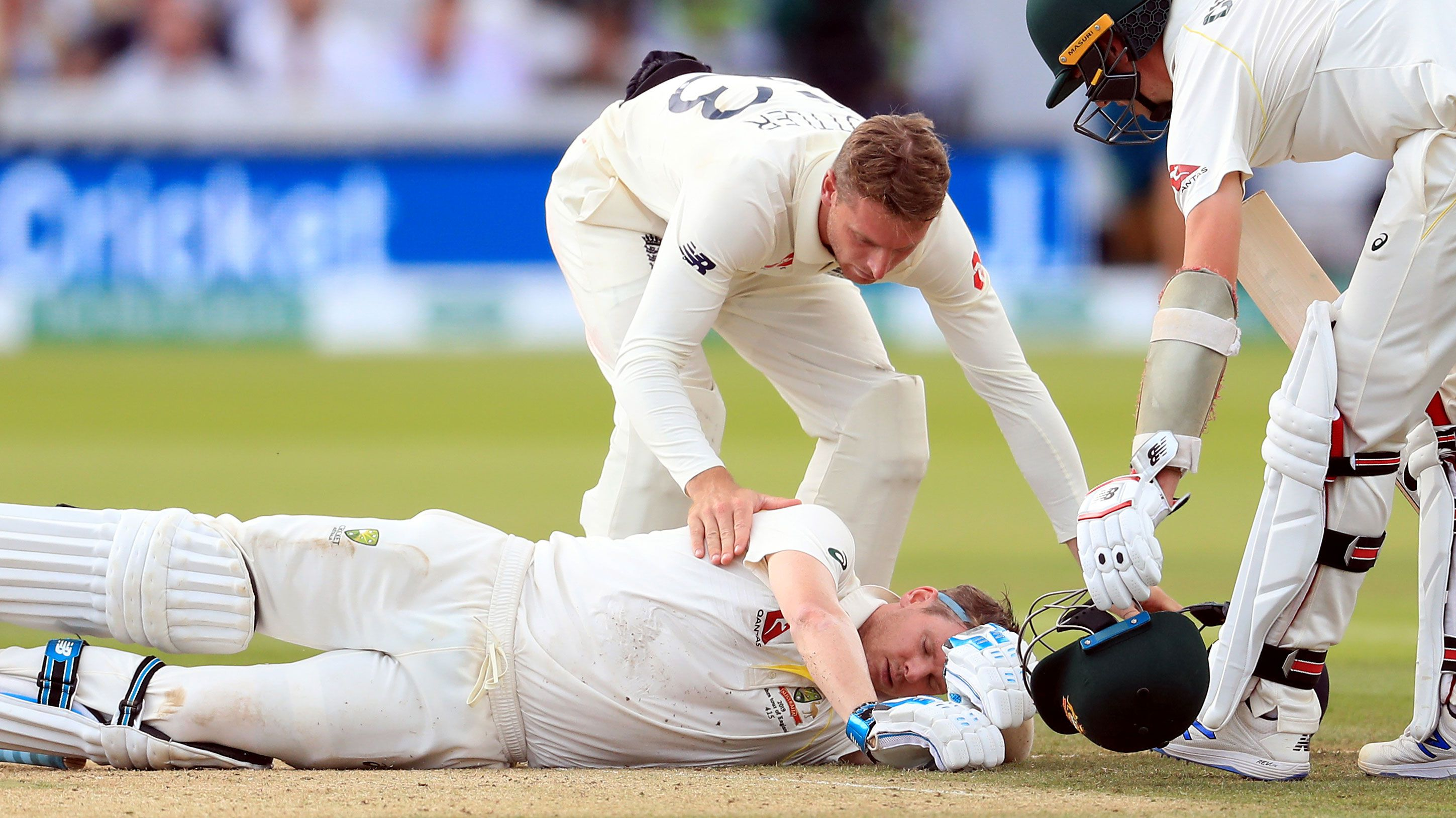 Players from both sides check on Steve Smith after he is felled by a Jofra Archer bouncer.