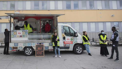 Volunteers distribute a free lunch during a multi-language information campaign on the COVID-19 coronavirus pandemic in the suburb of Tensta in Stockholm.