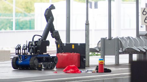 A remotely controlled bomb disposal robot approaches a red suitcase on a platform in Chemnitz Central Station in the region of Saxony, Germany on October 8. (AFP)