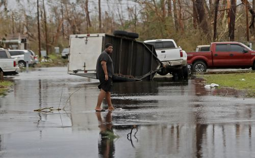 A man walks barefoot through the street with an overturned trailer in the distance.