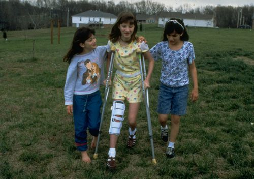 Christine Amer, 13, on crutches walking with help from her sisters after being shot during the shooting attack at Jonesboro Westside Middle School by gunmen Mitchell Johnson, 13, and Drew Golden, 11.