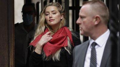 American actress Amber Heard waves at the media as she arrives at the High Court in London, Thursday, July 23, 2020.