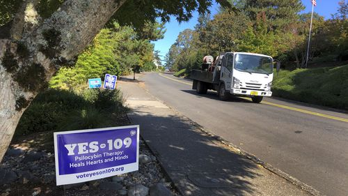 A truck drives past a sign supporting a ballot measure that would legalise controlled, therapeutic use of psilocybin mushrooms. War veterans with PTSD, terminally ill patients and others suffering from anxiety are backing the ballot measure.