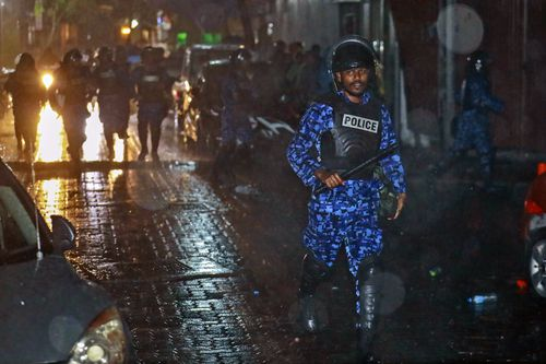A Maldives policeman charges with baton towards protesters after the government declared a 15-day state of emergency. Picture: AAP