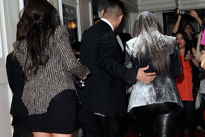 """Kim Kardashian took it on the chin (and the face, and the hair, and the clothes) when a crazy """"fan"""" dumped a bag of flour all over her at the launch of her new fragrance True Reflection."""
