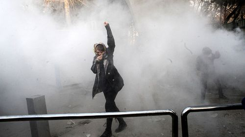 Iranian students clash with riot police during an anti-government protests around the Tehran University in Tehran. (AAP)