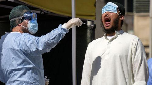 A man has a swab being taken to test for COVID-19 outside a healthcare center in Rome.
