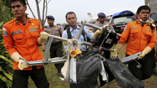 National Search and Rescue Agency personnel carry seats from AirAsia Flight 8501. (AAP)
