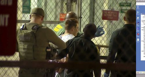 Nikolas Cruz is taken into custody by police after the massacre last night. Picture: AAP