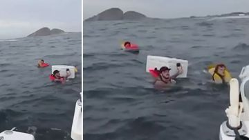 Mates cling to eskies as boat sinks