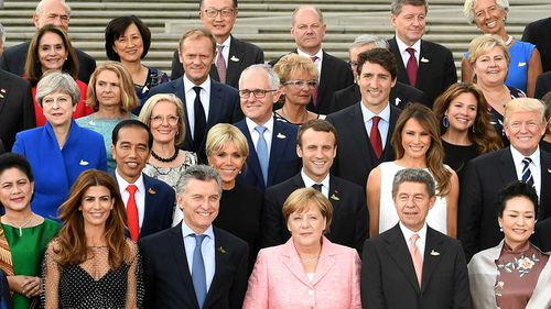 G20 leaders and their spouses gather for a group photo.
