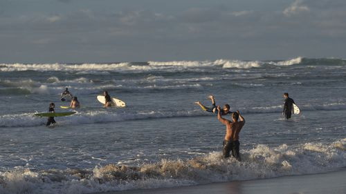Swimmers and surfers are pictured at Wategos Beach in Byron Bay.