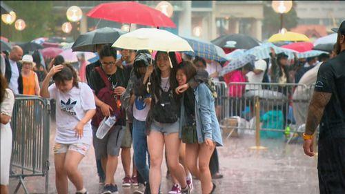 Rain has fallen on Sydney, sending the revellers dashing for cover.