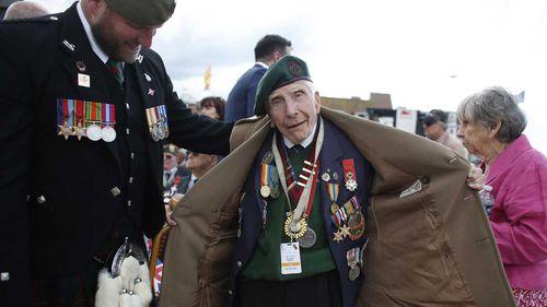 British D-Day veteran Harry Billinge opens his coat to show his medals.