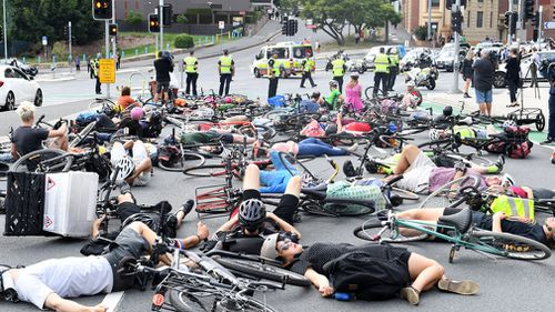 Cyclists block traffic during a 'Die-In' protest, obstructing peak-hour traffic at the Stanley and Vulture Street intersection. (AAP)