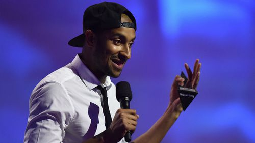 Triple J host Matt Okine accepts his award for best comedy release at the ARIAs. (AAP)
