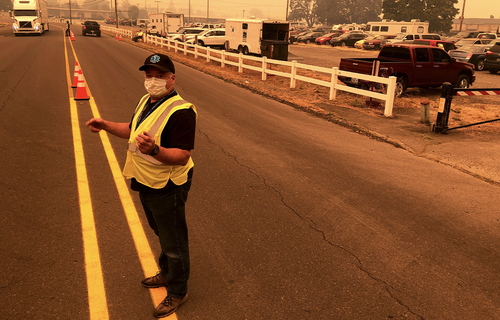 Under a smoke-filled sky, volunteer Shawn Daley directs traffic into the parking lot an evacuation center at the Oregon State Fairgrounds, which was crowded with hundreds of cars, pickup trucks and campers of evacuees, in Salem on Tuesday, Sept. 8, 2020.