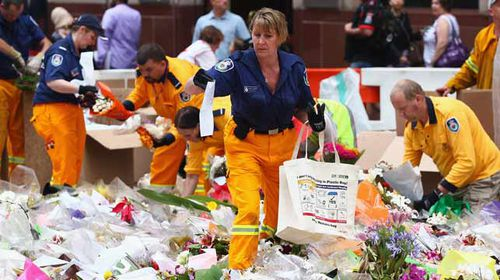 Volunteers pack up the floral tributes in Martin Place ahead of an expected rain shower. (Getty)