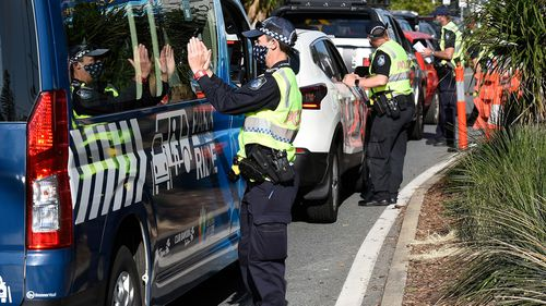 Police direct motorists at the Coolangatta border check point  in the Gold Coast.