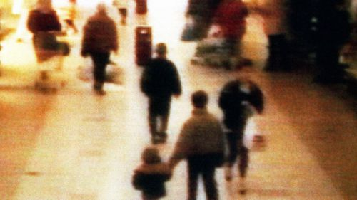 A still from CCTV shows two-years old James Bulger holding the hand of an unknown man as leaving a shopping center in Bootle, on February 16, 1993. (AAP)