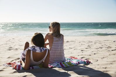 Friends sitting on a beach in Perth