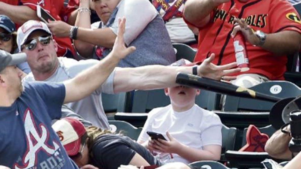 Shaun Cunningham blocks the flying bat as his son, Landon, looks up. (Supplied)