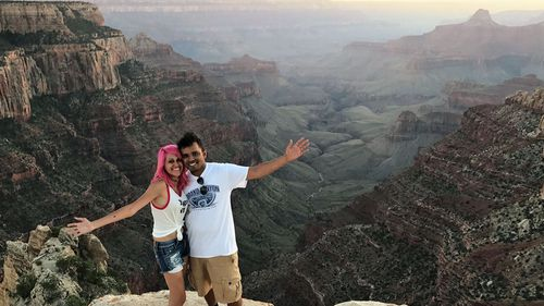 The 'travel obsessed' couple pose at the Grand Canyon.