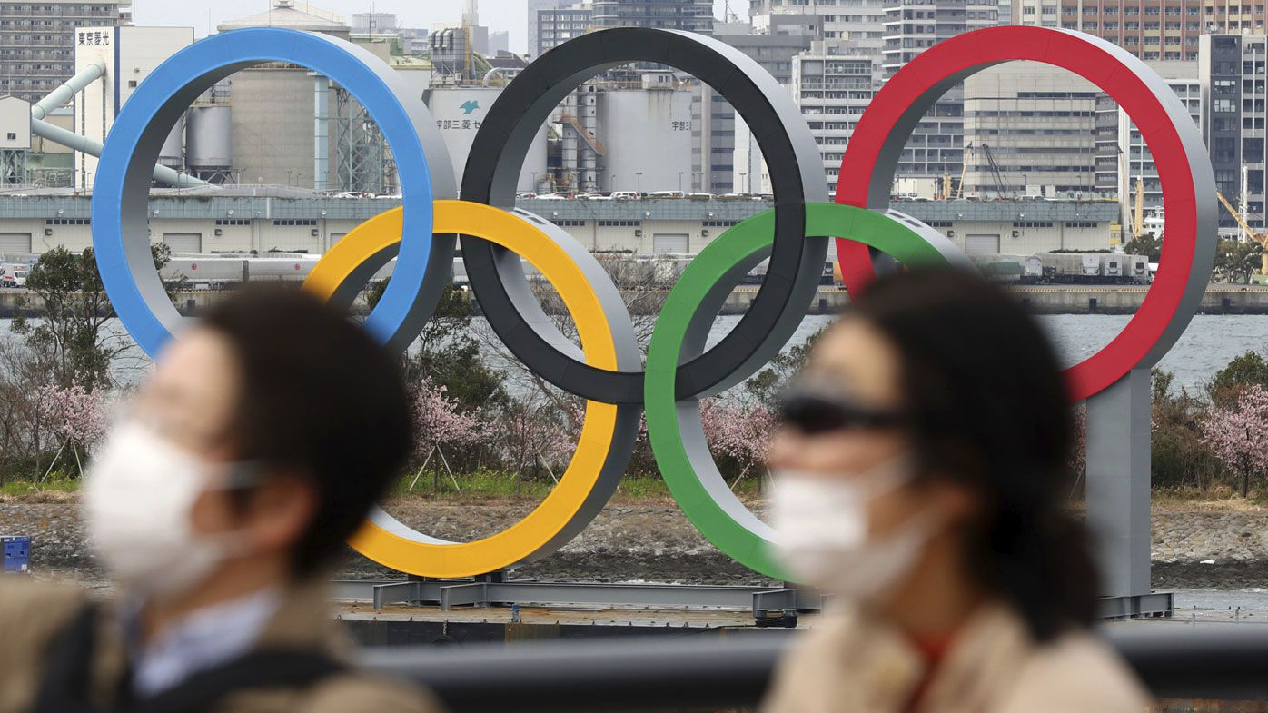 People wearing a mask walk near the Olympics' mark in Odaiba, Tokyo on February 22, 2020, amid the outbreak of a new coronavirus in Japan.