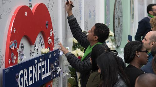 People gather  to sign a Grenfell tribute sign. Picture: Getty