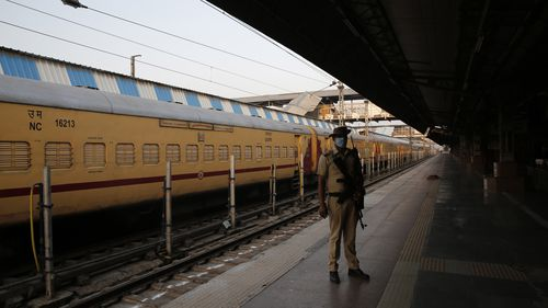 A security man stands guard at a deserted railway station in Prayagraj, India.