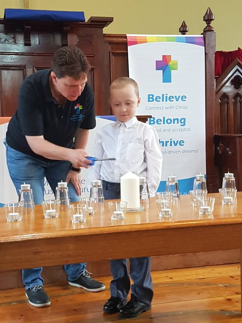 Jack and Pastor Becky lighting candles during church.