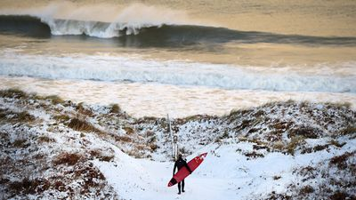 January 14, 2015: Pro surfer Alastair Mennie makes his way towards the beach at Portrush in Antrim, Northern Ireland.  <br><br> The province experienced heavy snowfall as a cold weather front hit the northern part of the United Kingdom today causing major traffic disruption and school closures. <br><br>  Photo by Getty Images.
