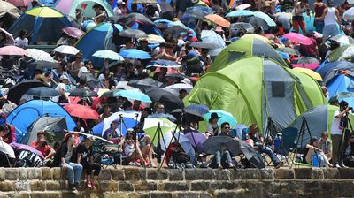 Thousands of New Year's Eve revellers with tents and tripods take up their positions ahead of the revelry. (AAP)