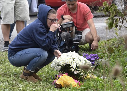 A woman kneels in mourning at the site where 20 people were killed when a limousine ran through a stop sign on its way to a birthday party.