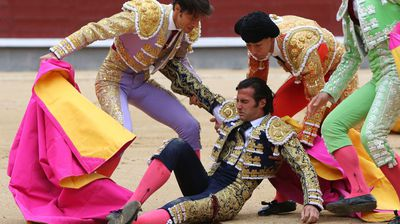 Assistants help Mora who was carried out of the prestigious Las Ventas bullring.