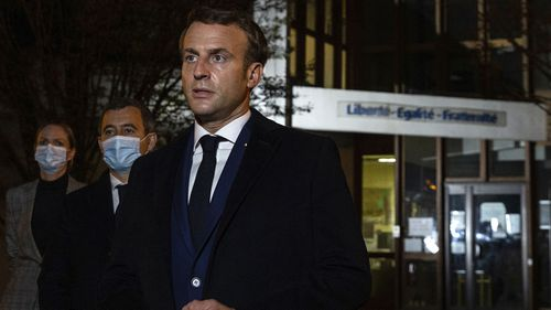 French President Emmanuel Macron, flanked by French Interior Minister Gerald Darmanin, second left, speaks in front of a high school Friday Oct.16, 2020 in Conflans Sainte-Honorine, northwest of Paris