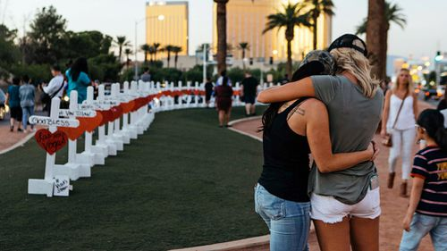 """A memorial displaying 58 crosses by Greg Zanis stands at the """"Welcome To Las Vegas Sign"""" in Las Vegas. (AAP)"""