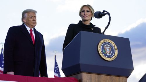 President Donald Trump listens as First Lady Melania Trump speaks before boarding Air Force One at Andrews Air Force Base, Md., Wednesday, Jan. 20, 2021.