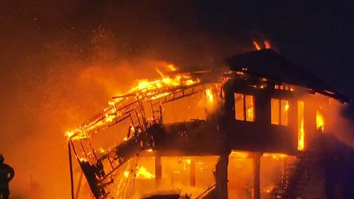 Dozens of firefighters worked to contain the fire, which caused 75 percent of the home to collapse onto its foundations.