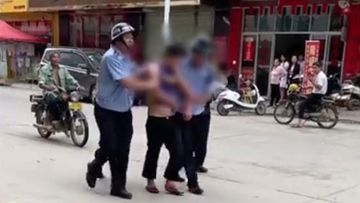 A suspect is arrested by police after a stabbing rampage at a kindergarten in Beiliu City.