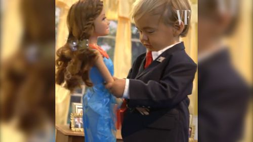 Mini Trump plays with building blocks and a doll during the Vanity Fair Video.