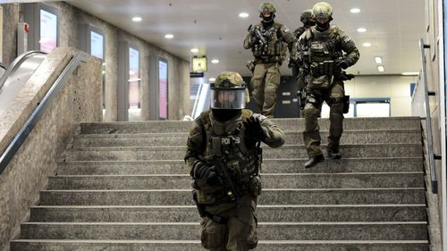 Heavily armed police run through a stairwell at a train station in Munich. (AFP)