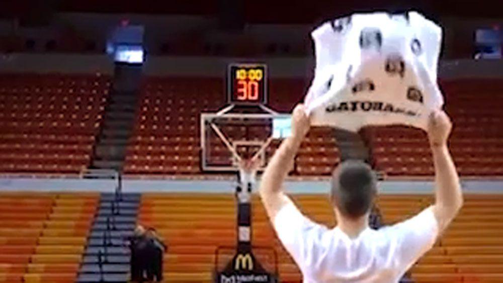 Basketballer uses towel to hit half-court shot