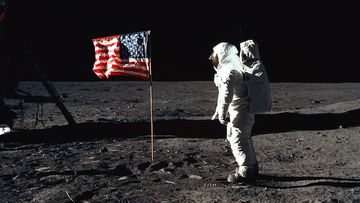 Astronaut Buzz Aldrin stands next to the US flag on the moon on the Apoillo 11 mission.