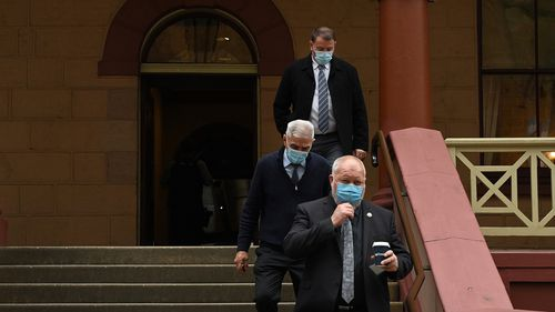 A group of men wearing face masks leave NSW Parliament House after NSW Agriculture Minister Adam Marshall tested positive for COVID-19.