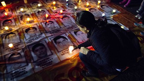 A woman places a candle on photos of the missing students during a protest against the disappearance of 43 students from the Isidro Burgos rural teachers college, in Mexico City, Wednesday, Oct. 22, 2014. Tens of thousands marched in Mexico City's main avenue demanding the return of the missing students.