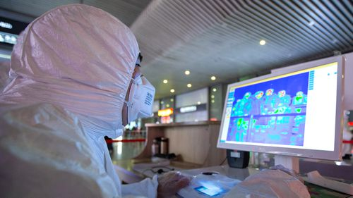 Chinese medical workers wearing protective clothing monitor body temperatures of passengers on a display for prevention of the new coronavirus at the Nanjing South Railway Station
