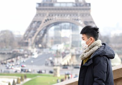 A tourist protects his face at the Eiffel Tower